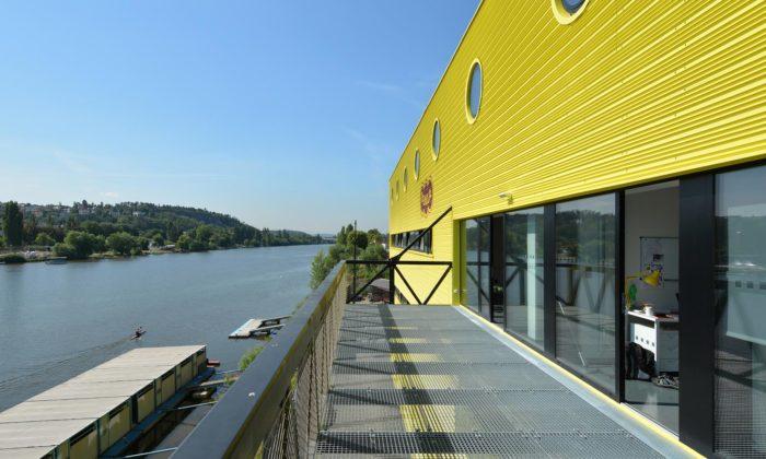 Na pražském břehu Vltavy nepřehlédnutelně žlutě září Loděnice Dukla