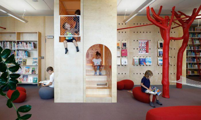 Lotyšsko má hravou dětskou knihovnu sčervenými stromy aprolézačkou