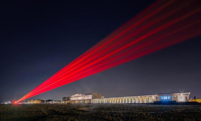 Na belgické pláži svítí bariéra zlaserových paprsků poukazující narozdělení společnosti