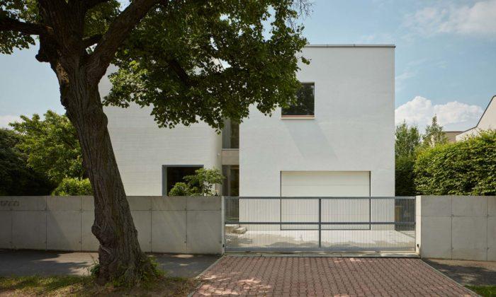Rodinný dům Lhotka jetvořen spojenými minimalistickými bílými hmotami